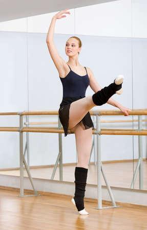 Tragen Trikot und Stulpen Ballerina tanzt in der Nähe barre und Spiegel im Studio