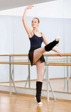 barre: Wearing leotard and warmers ballerina dances near barre and mirrors in studio