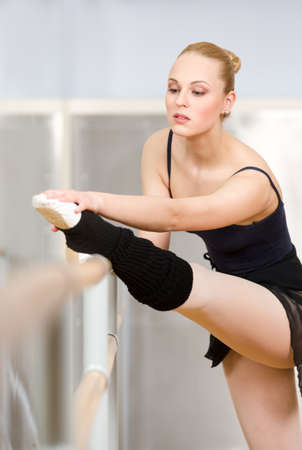 barre: Ballerina stretches herself near barre and mirrors in the dancing hall