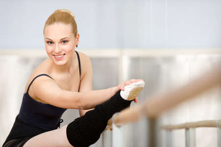 barre: Athlete stretches herself near barre and mirrors in the classroom