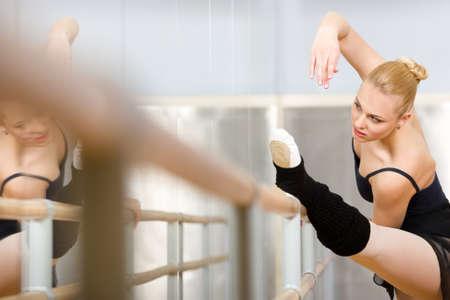 Ballerina erstreckt sich in der Nähe von Barre und Spiegel im Klassenzimmer