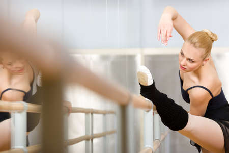 barre: Ballerina stretches herself near barre and mirrors in the classroom