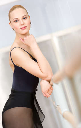 athletic wear: Portrait of standing near barre and mirrors ballerina wearing leotard and propping her head with hand Stock Photo