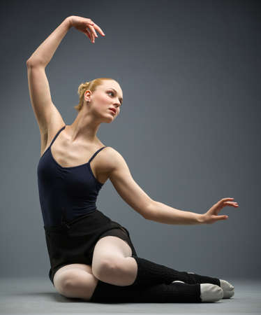 Dancing on the floor ballerina with her hand up, isolated on grey. Concept of elegant art and sportive hobby photo