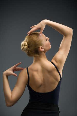 guardar silencio: Retrato de medio cuerpo de la bailarina con las manos arriba, aislado en gris. Concepto de arte elegante y afición deportiva