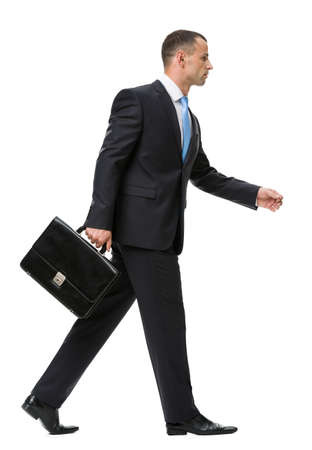 full body shot: Profile of walking with case businessman, isolated on white. Concept of leadership and success