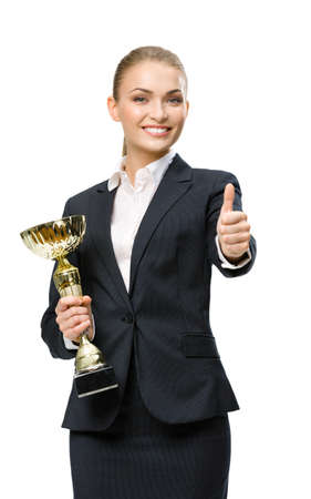 Half-length portrait of businesswoman keeping golden cup and thumbing up, isolated on white. Concept of victory and success photo