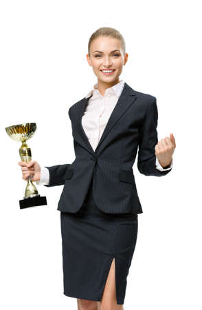Business woman keeping golden cup and fist up gesturing, isolated on white. Concept of victory and success photo