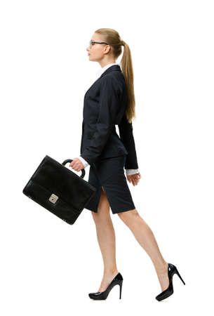 sideview: Profile of walking businesswoman handing suitcase, isolated on white. Concept of leadership and success