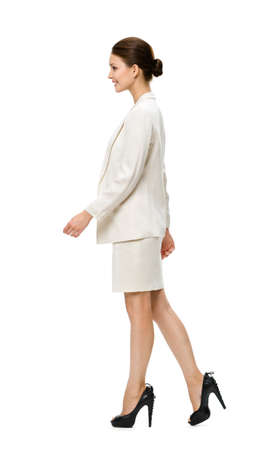 side job: Full-length profile of walking businesswoman, isolated on white. Concept of leadership and success