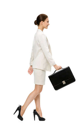 Profile of walking business woman with case, isolated on white. Concept of leadership and success photo