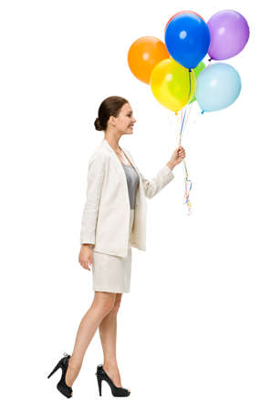 Full-length profile of business woman walking with colorful balloons, isolated on white. Concept of leadership and success photo