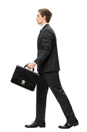 Full-length profile of walking with case business man, isolated on white. Concept of leadership and success photo