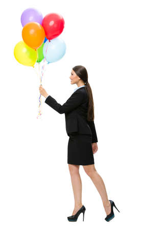 Full-length profile of business woman keeping colorful balloons, isolated on white. Concept of holiday and fun photo
