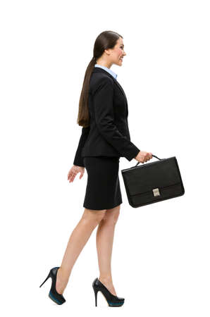 sideview: Full-length profile of walking businesswoman with case, isolated on white. Concept of leadership and success Stock Photo