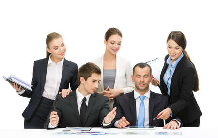 Group of executives working while sitting at the table, isolated on white. Concept of teamwork and cooperation photo
