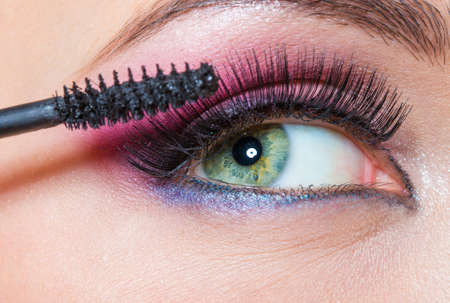 Close up of female eye with brilliant make-up and brush applying mascara on eyelashes photo