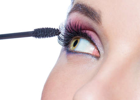 Close up of female eye with bright make-up and brush applying mascara on eyelashes, isolated on white photo