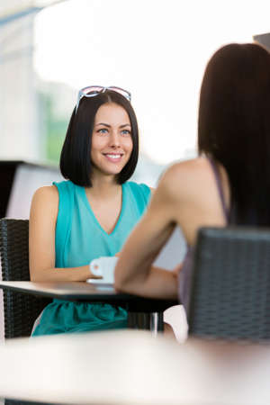 adult intercourse: Girl wearing blue dress and sunglasses sits at the table of the cafeteria and talks with friend