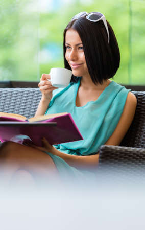 pleasure of reading: Girl wearing blue dress and sunglasses sits at the table of the bar and reads book with cup of coffee