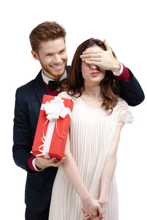 Giving a present man covers eyes of his pretty girlfriend, isolated on white photo