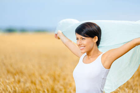 Girl hands silk scarf against rye field. Concept of freedom and happiness photo