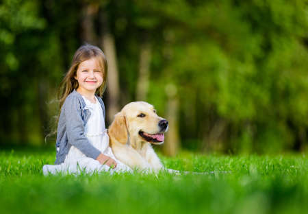 Little girl sitting on the grass with labrador retriever in the summer park