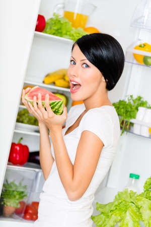 vertical fridge: Woman eats watermelon near the opened refrigerator full of vegetables and fruit. Concept of healthy and dieting food