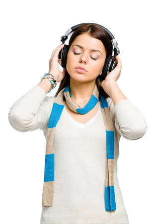 Half-length portrait of teenager with eyes closed listening to music in headphones, isolated on white photo