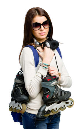Half-length portrait of teenager handing roller skates and wearing sunglasses, earphones and rucksack, isolated on white photo