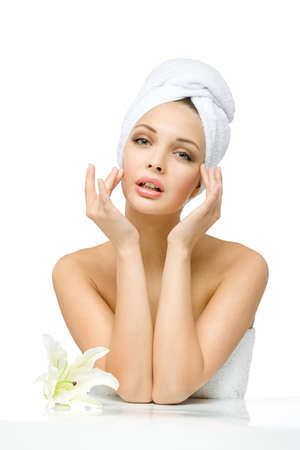 Sexy woman with towel on head touches her face sitting near white lily, isolated on white. Concept of healthcare, beauty and youth photo