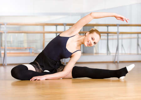Bending ballet dancer stretches herself on the wooden floor in the classroom Stock Photo