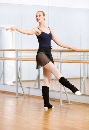 Wearing leotard and warmers ballet dancer dances near barre and mirrors in studio Stock Photo