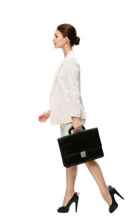 mujer con maleta: Perfil de la mujer de negocios que recorre con la maleta, aislado en blanco. Concepto de liderazgo y éxito Foto de archivo