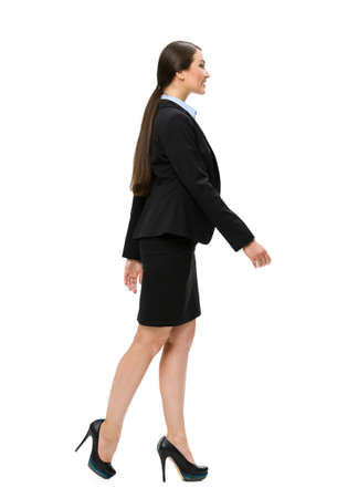 Full-length profile of walking business woman, isolated. Concept of leadership and success photo