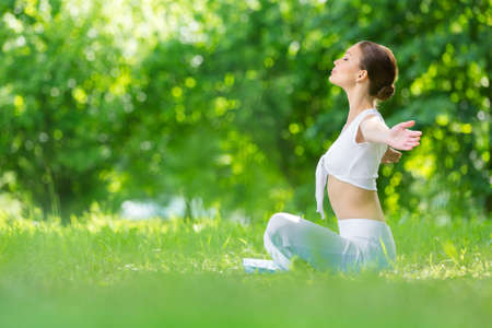 Profile of woman sitting in lotus position with outstretched arms. Concept of healthy lifestyle and relaxation Stockfoto