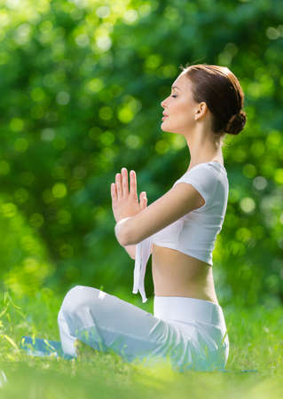 sideview: Profile of woman who sits in lotus position prayer gesturing. Concept of healthy lifestyle and gratitude Stock Photo