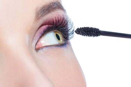 Close up of female eye with brilliant make-up and brush applying mascara on eyelashes, isolated on white photo