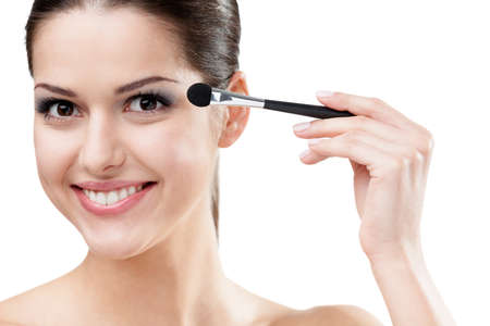 makeup brush: Woman applying make-up with cosmetic brush, isolated on white. Beauty procedures