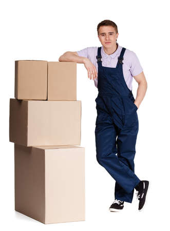 Young delivery man in overalls with pasteboard boxes, isolated on white. Transportation service photo