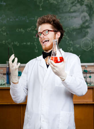 meanness: Mad professor laughs handing conical flask with red liquid in his laboratory