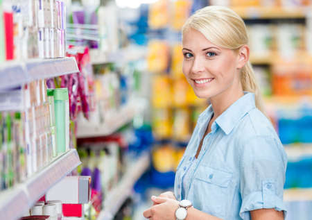 Portrait of young girl at the market standing near the shelves with cosmetics photo