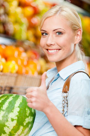 Girl at the shop choosing fruits and vegetables hands watermelon thumbs up Stock Photo - 22809068