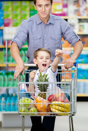 Little boy with fists up suiting in shopping trolley with food, father drives the cart