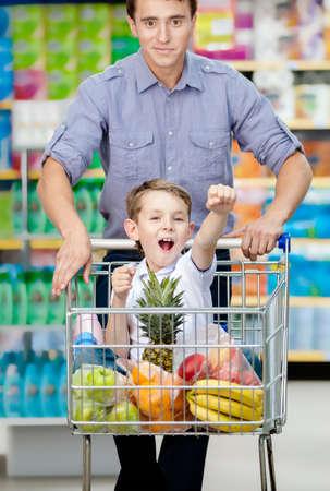 Kleiner Junge mit Fäusten bis suiting in Einkaufswagen mit Lebensmitteln treibt Vater den Warenkorb Lizenzfreie Bilder