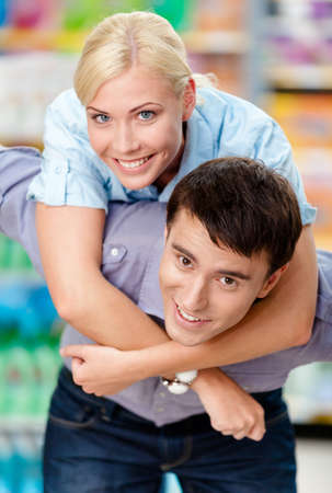 Girl embraces man in the supermarket. Concept of happy relationship and affection Stock Photo - 22809069