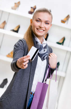Woman showing credit card in footwear shop with great variety of stylish shoes photo