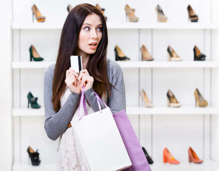 doubtfulness: Girl holds credit card in footwear shop with great variety of stylish shoes Stock Photo
