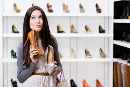 Vrouw houdt twee stijlvolle pompen in het winkelcentrum en kunnen niet kiezen voor de een voor haar Stockfoto