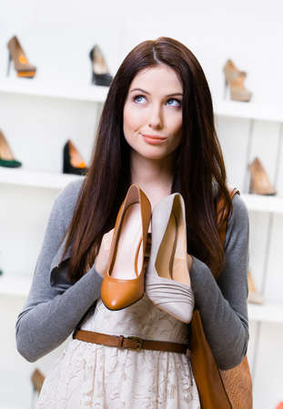 doubtfulness: Woman holds two shoes in the shopping mall and cant choose the one for her Stock Photo